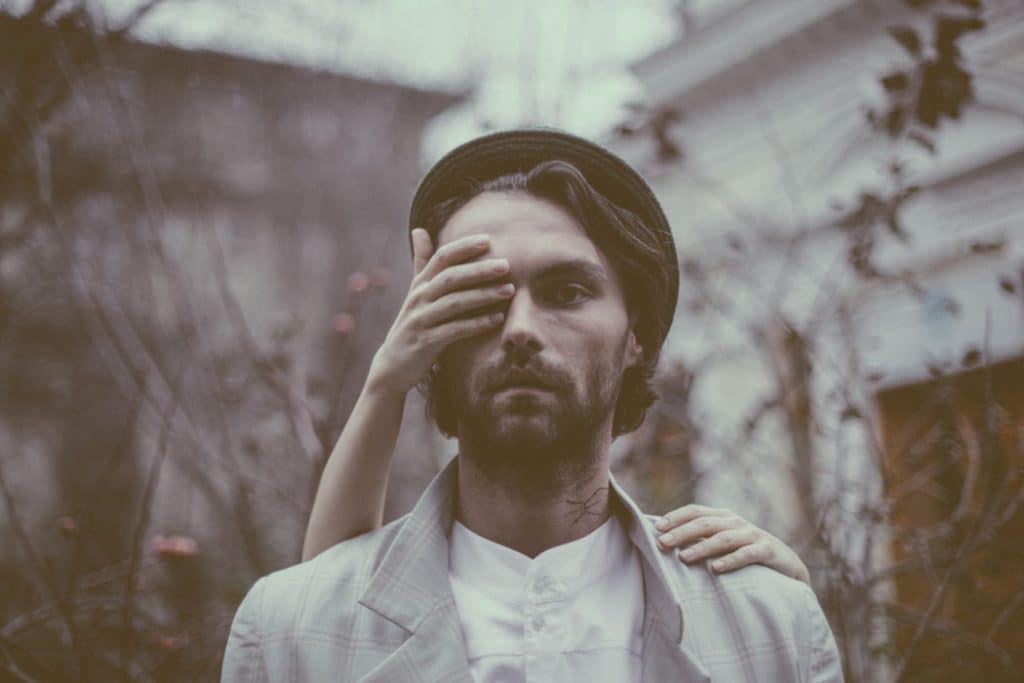 Homem branco, em pé, com expressão triste, com a mão de outra pessoa tapando um de seus olhos.