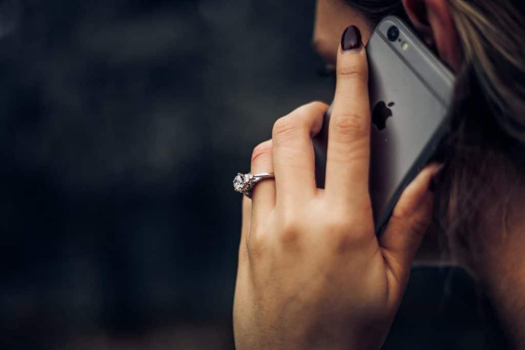 mulher de costas, segurando seu celular perto da orelha, como se estivesse falando em uma ligação.