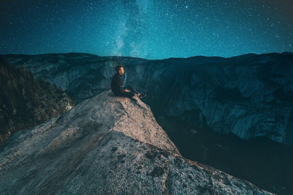 Homem sentado na beira de um penhasco, observando o céu azul da noite estrelada.