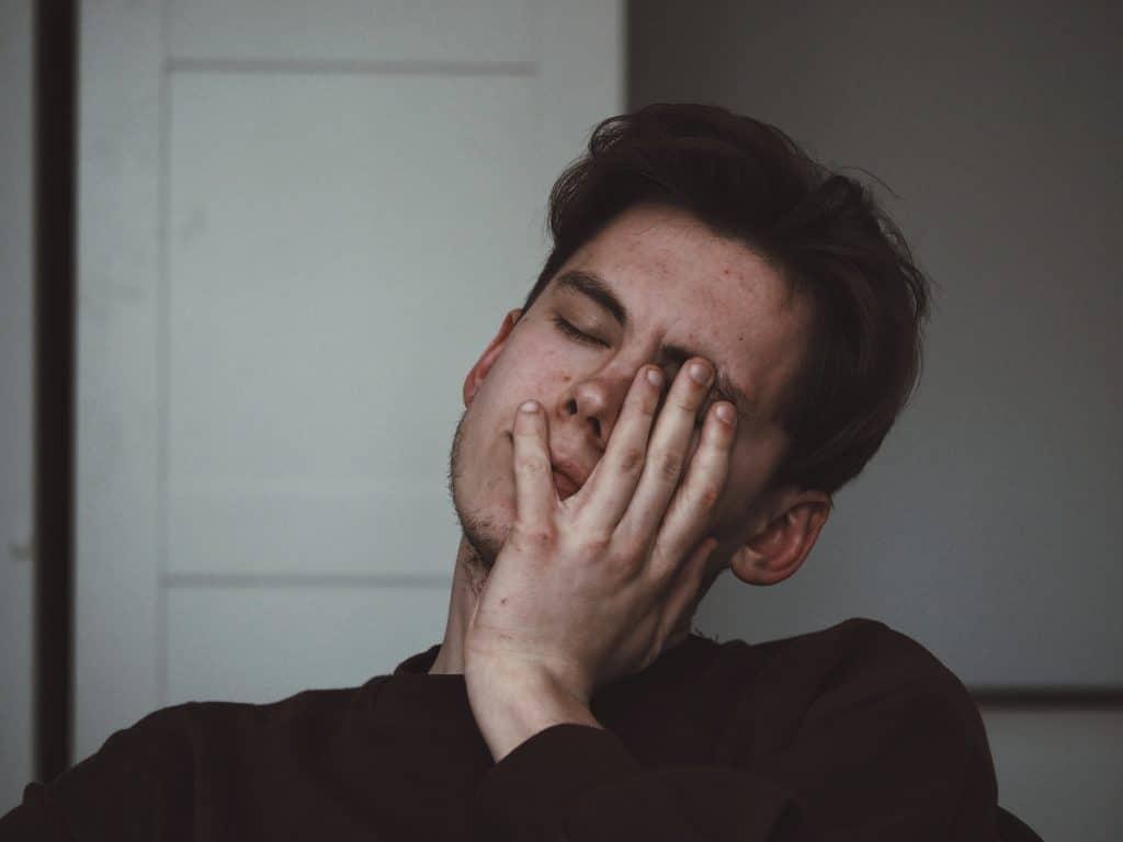 homem sentado em uma cadeira, com os olhos fechados e expressão de cansaço, apoiando seu rosto em uma de suas mãos.