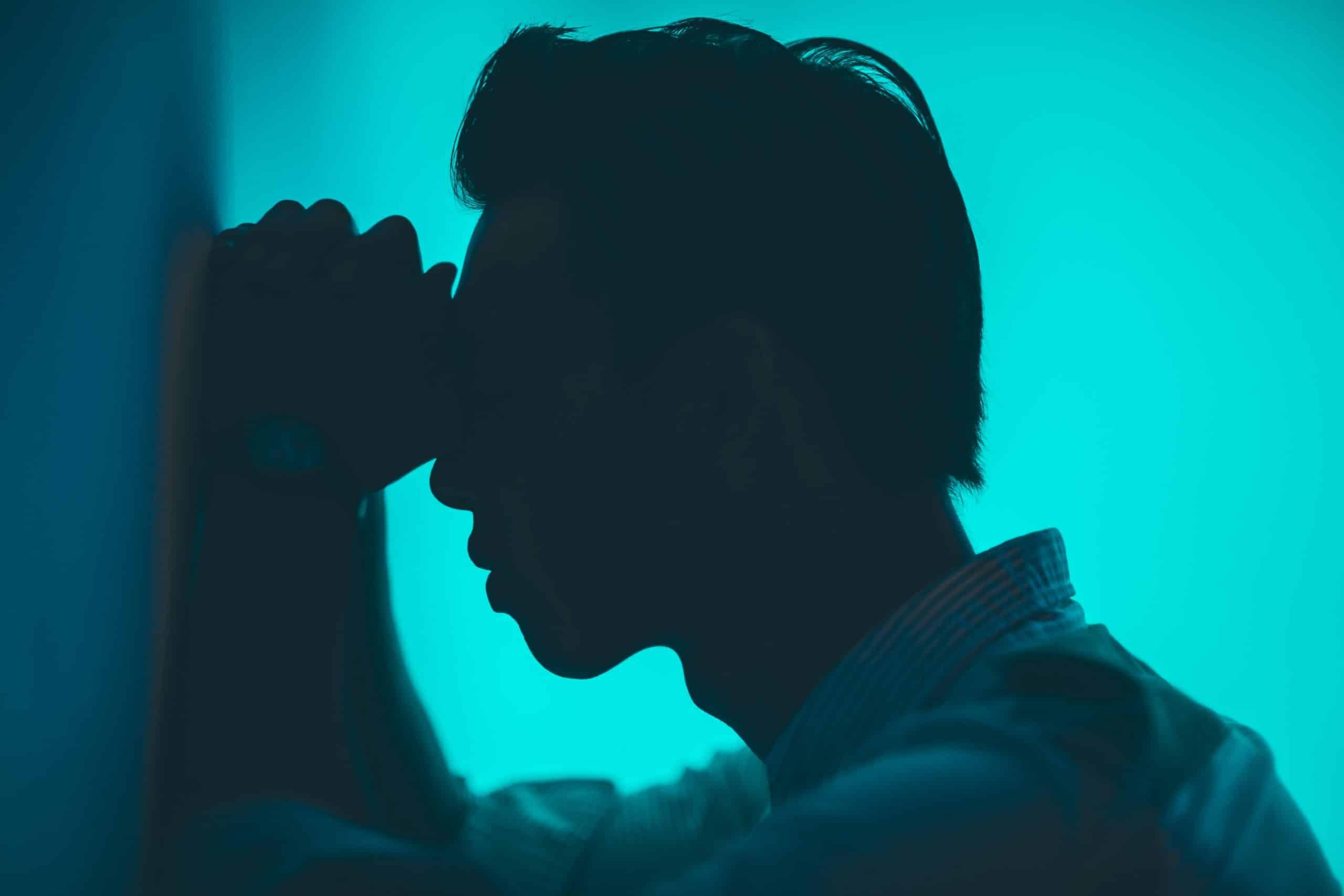Silhueta de um homem de perfil com o rosto apoiado em suas mãos fechadas que encostadas na parede, indicando cansaço, energia negativa.