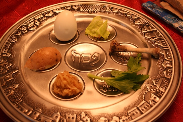 Prato típico judaico decorado com ilustrações de casas em suas bordas contendo sete divisões dispostas de maneira circular. Cada círculo possui um alimento, como ovo, alface, frango, batata... No meio dos seis círculos, há um círculo maior com uma inscrição judaica.