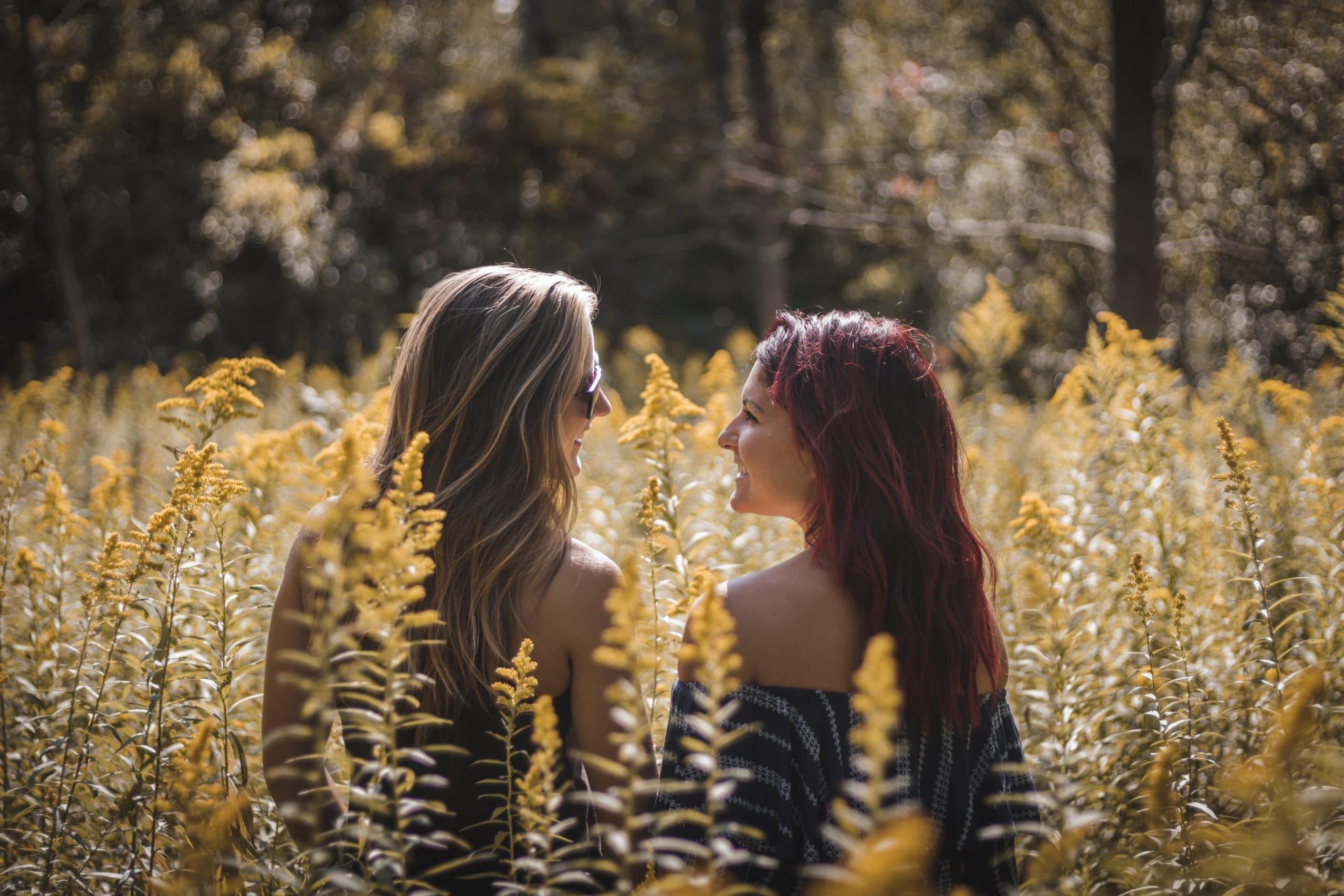 Duas meninas no campo de costas se olhando e sorrindo