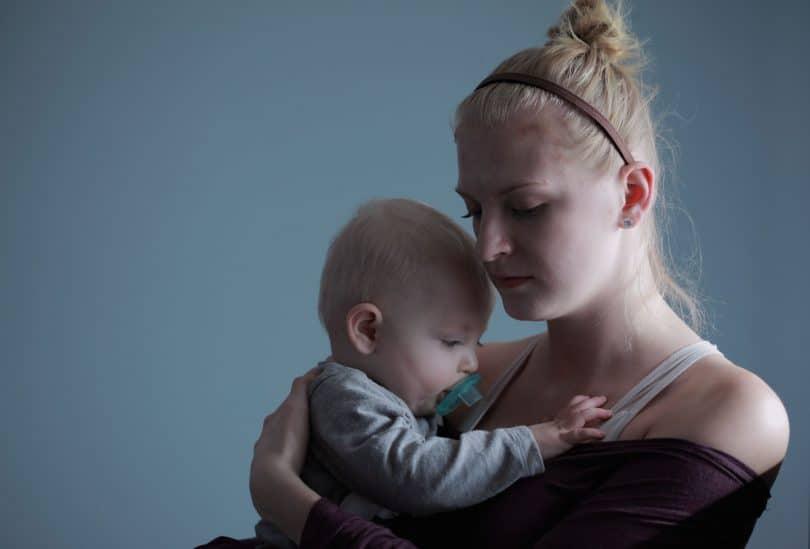 Mãe com olhar triste com filho bebê no colo