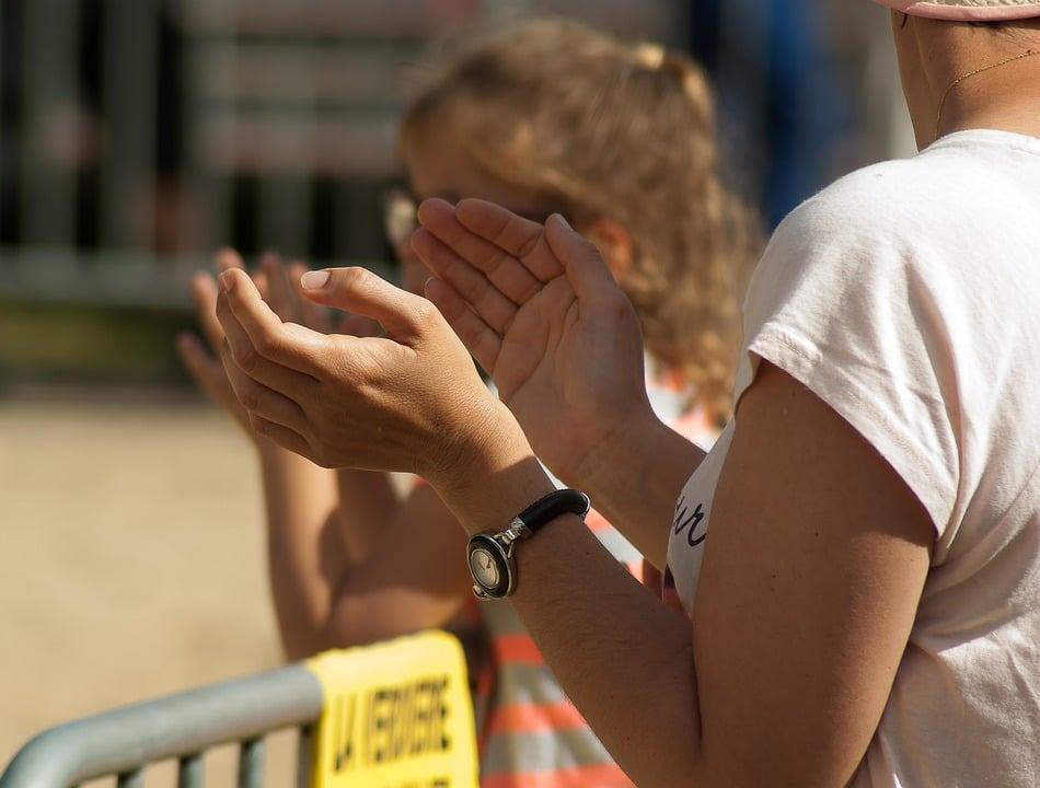 Foto de mulher branca aplaudindo algo em uma praça.