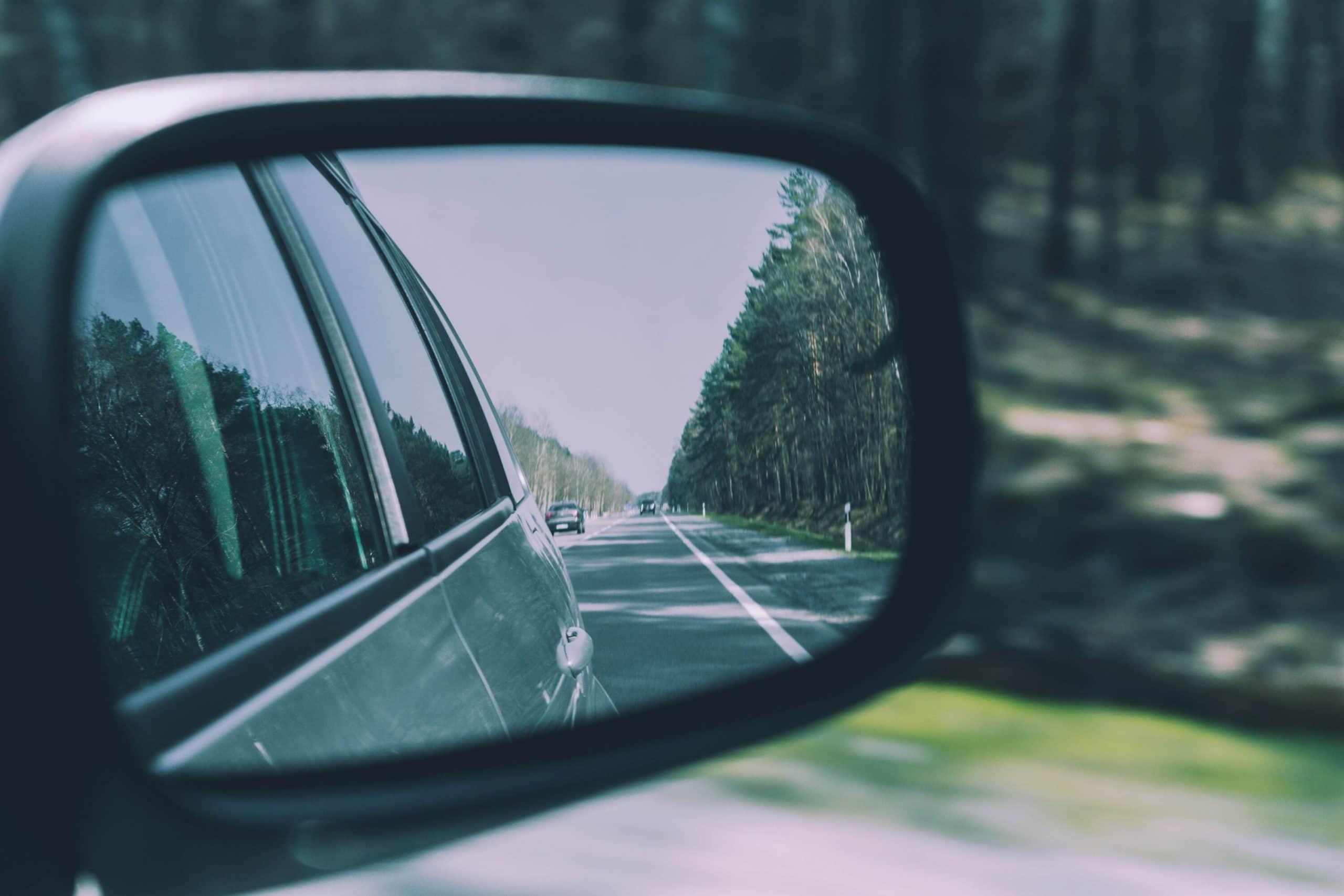 Rodovia vista através do retrovisor lateral de um carro