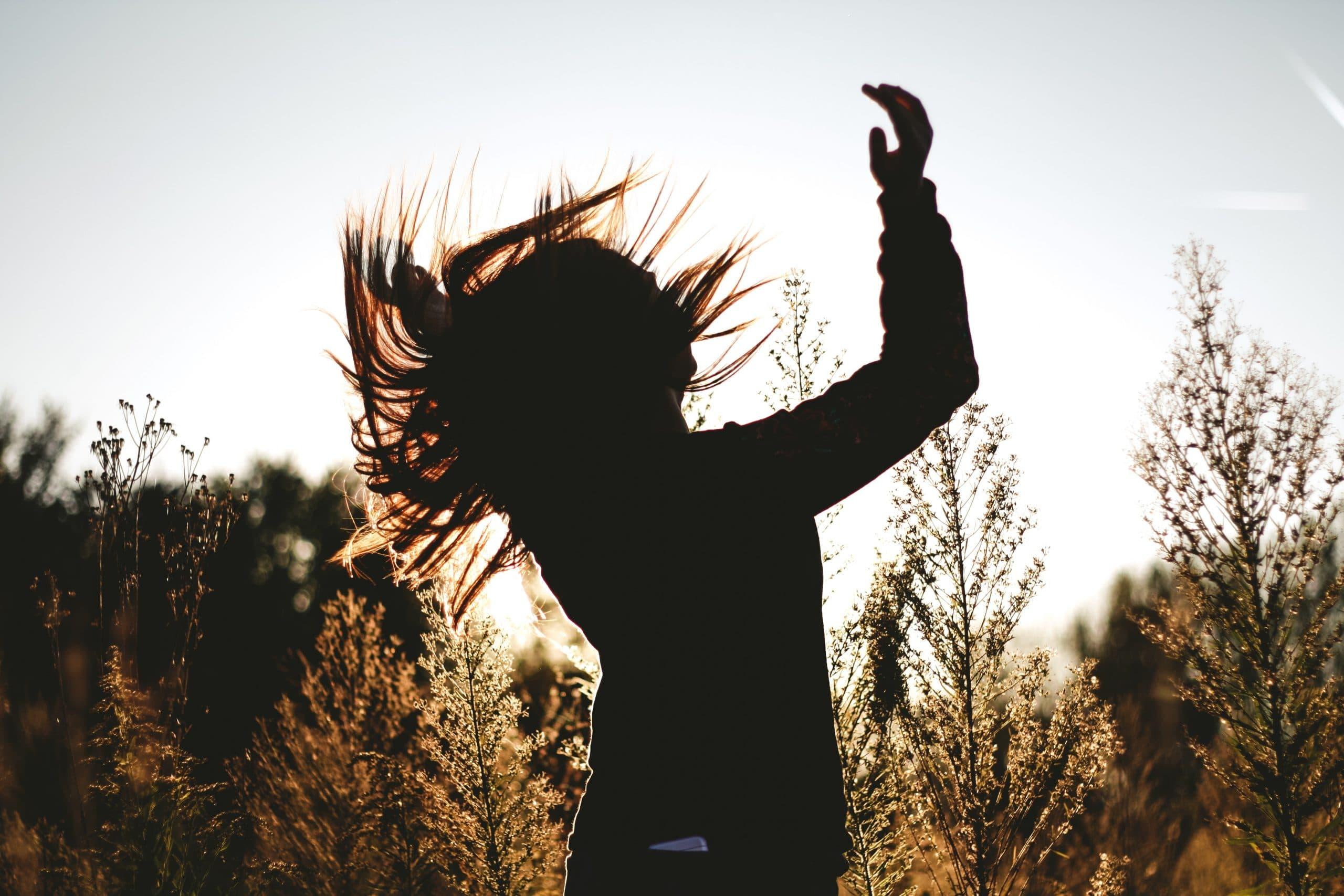 Silhueta de mulher dançando com cabelos ao vento no meio de plantas