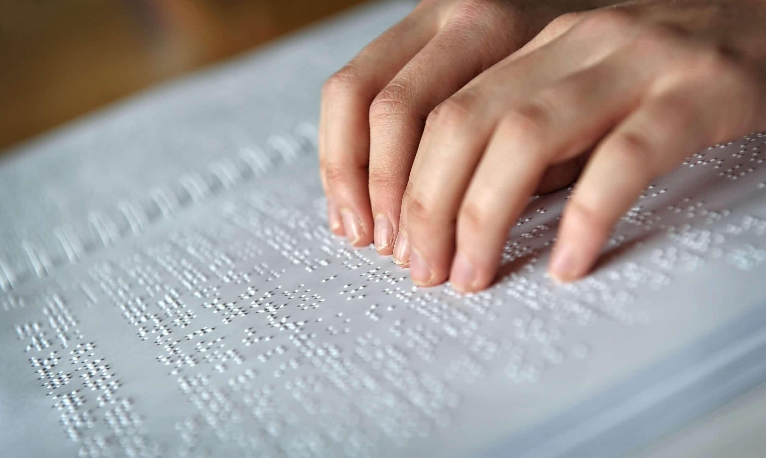 Mãos juntas lendo livro em Braille