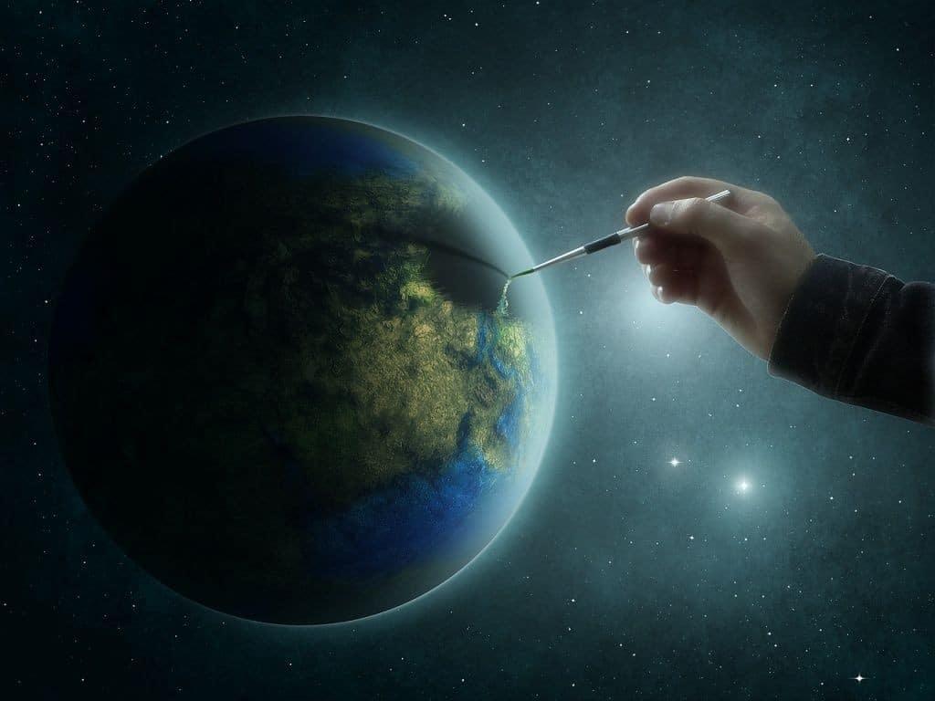 mão segurando um pincel enquanto pinta a terra
