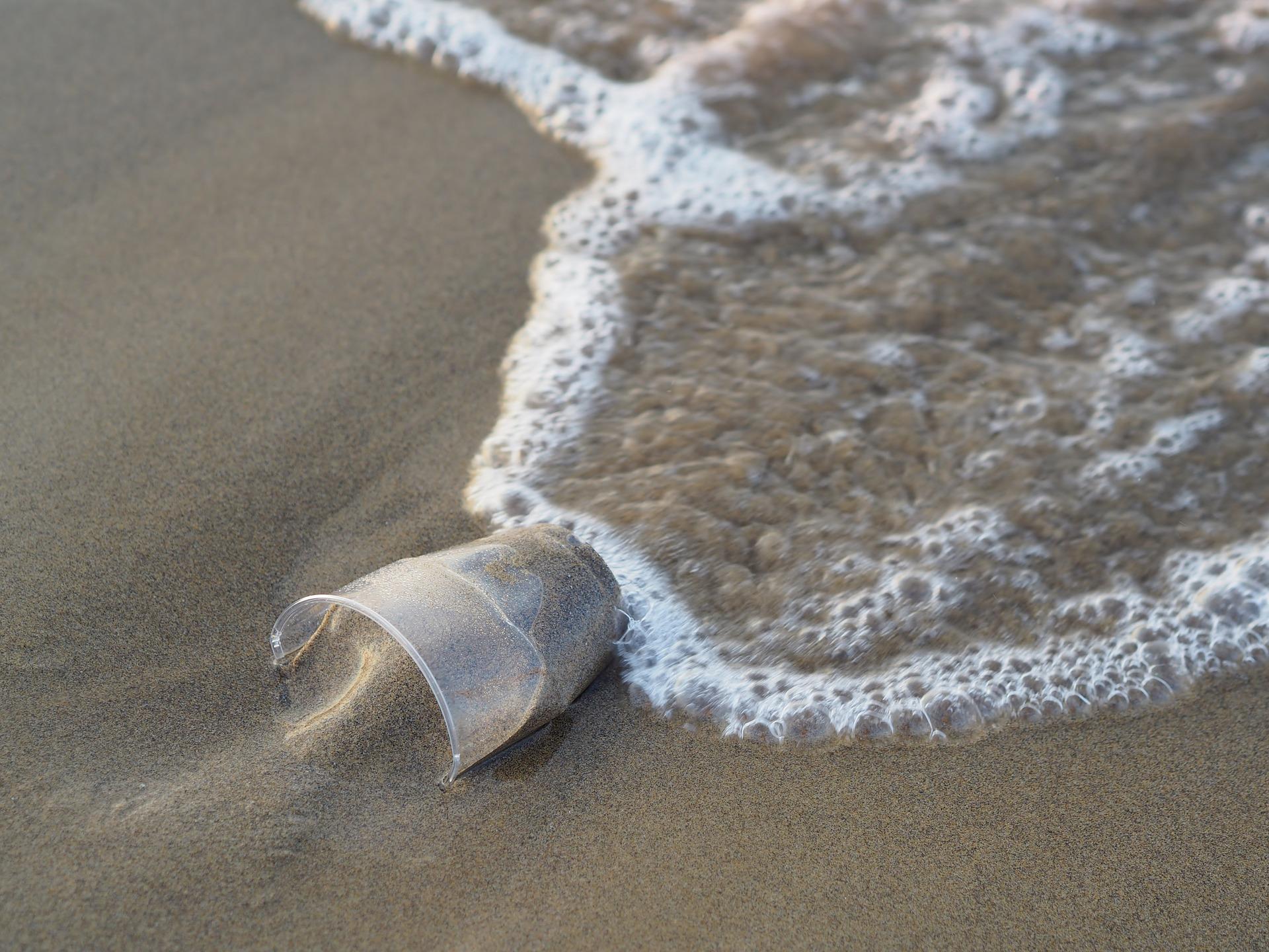 Copo de plástico preso na areia, com ondas do mar alcançando-o.