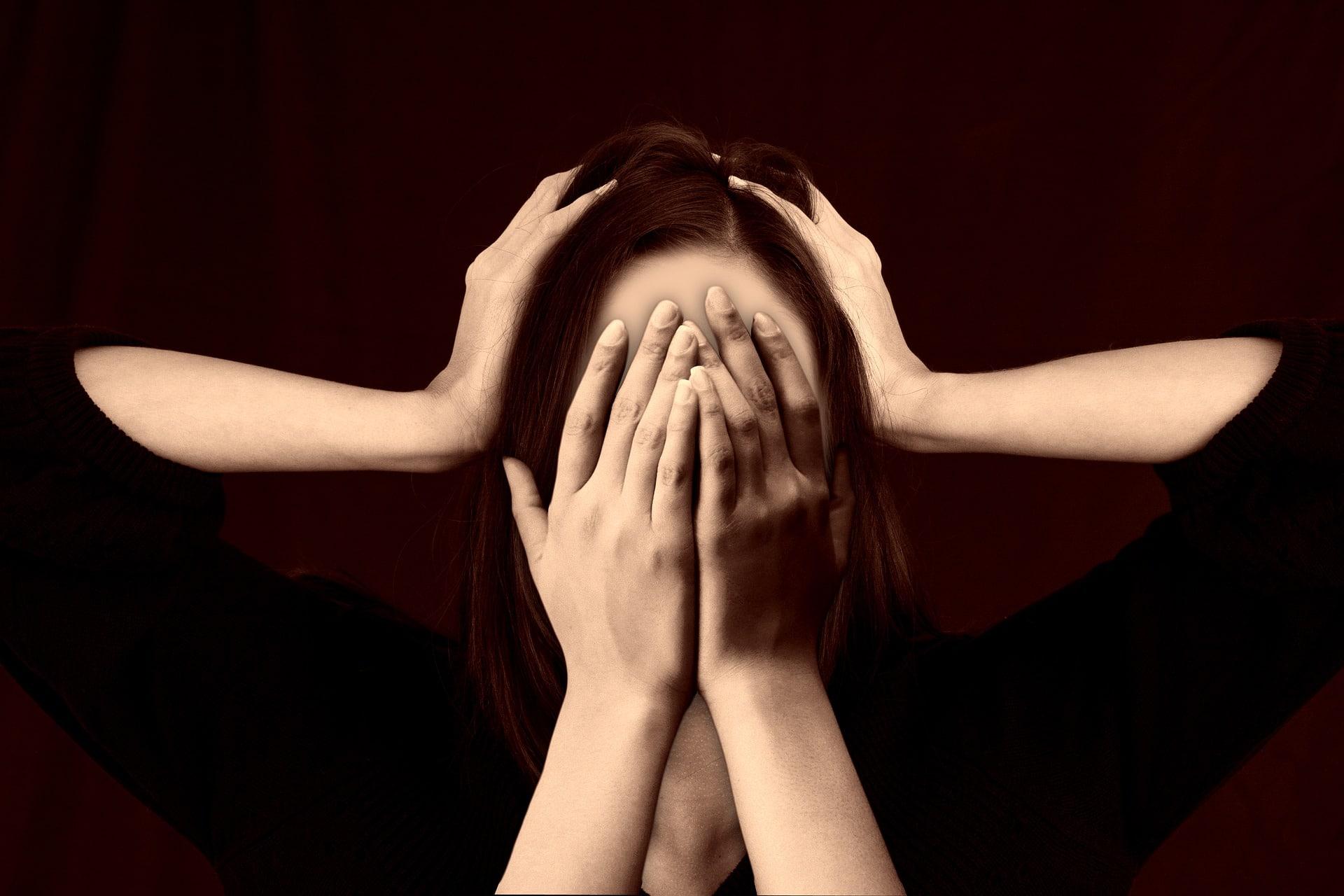 Mulher sobre um fundo preto, com as mãos cobrindo o rosto em sinal de desespero. Outras duas mãos seguram sua cabeça.