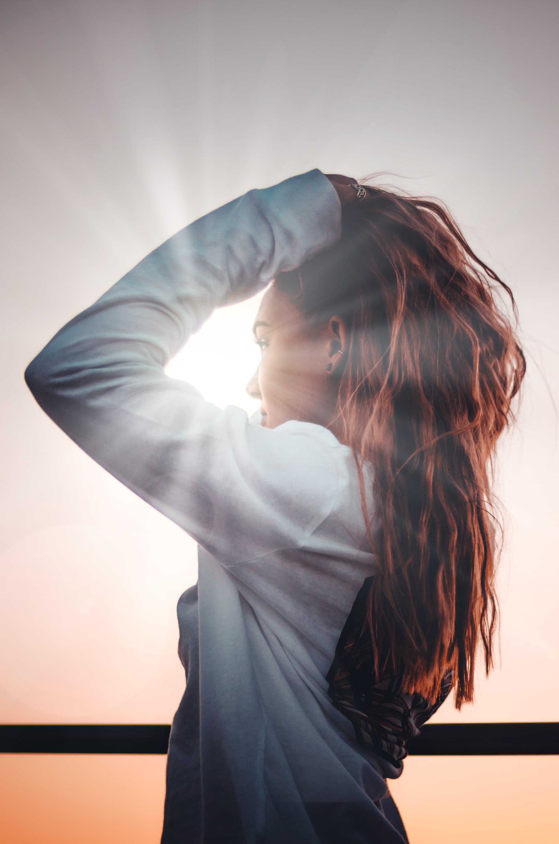 Garota de perfil de blusa cinza com um dos braços levantados colocando seus longos cabelos castanhos para trás. Ao fundo, o brilho do sol incide sobre sua face.