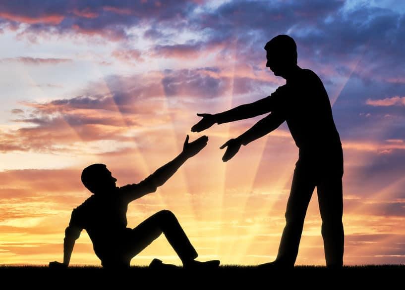 Silhueta de um homem caído, com a mão estendida para receber ajuda de outro
