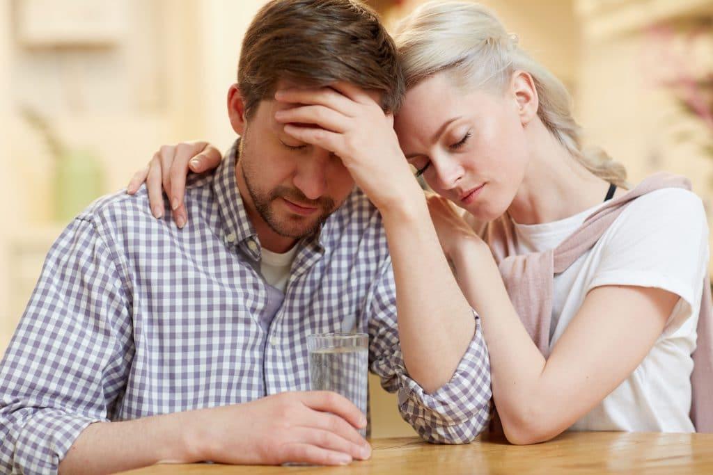 Homem e mulher, ambos brancos e jovens, sentados em uma. Ambos com expressão de preocupados. A mulher está abraçando o homem.