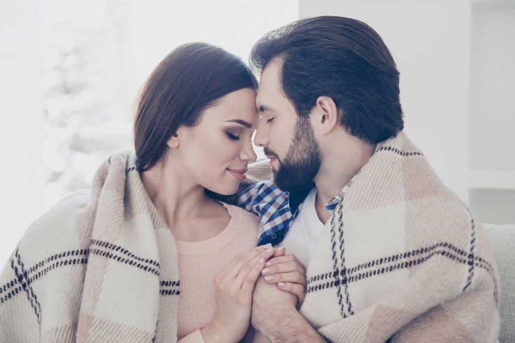 Casal sentado em um sofá, abraçado, se cobrindo com um cobertor, encostando seus rostos um no outro.