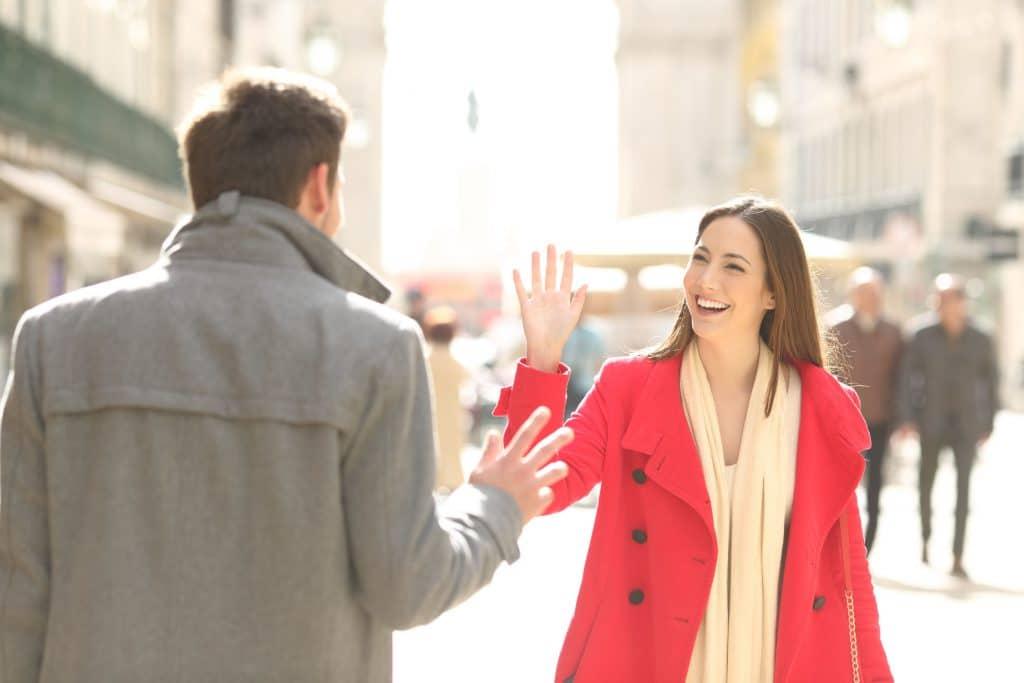 Mulher branca, jovem, sorridente, andando na rua, cumprimentando de longe um homem.