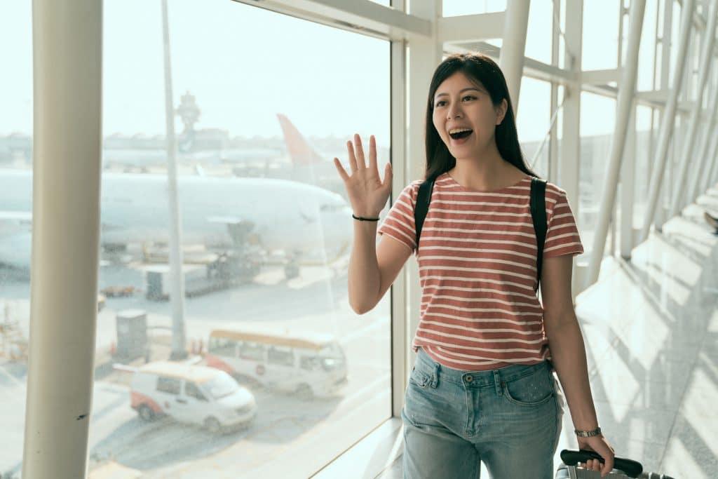 Mulher asiática, jovem, sorridente, cumprimentando alguém em um aeroporto