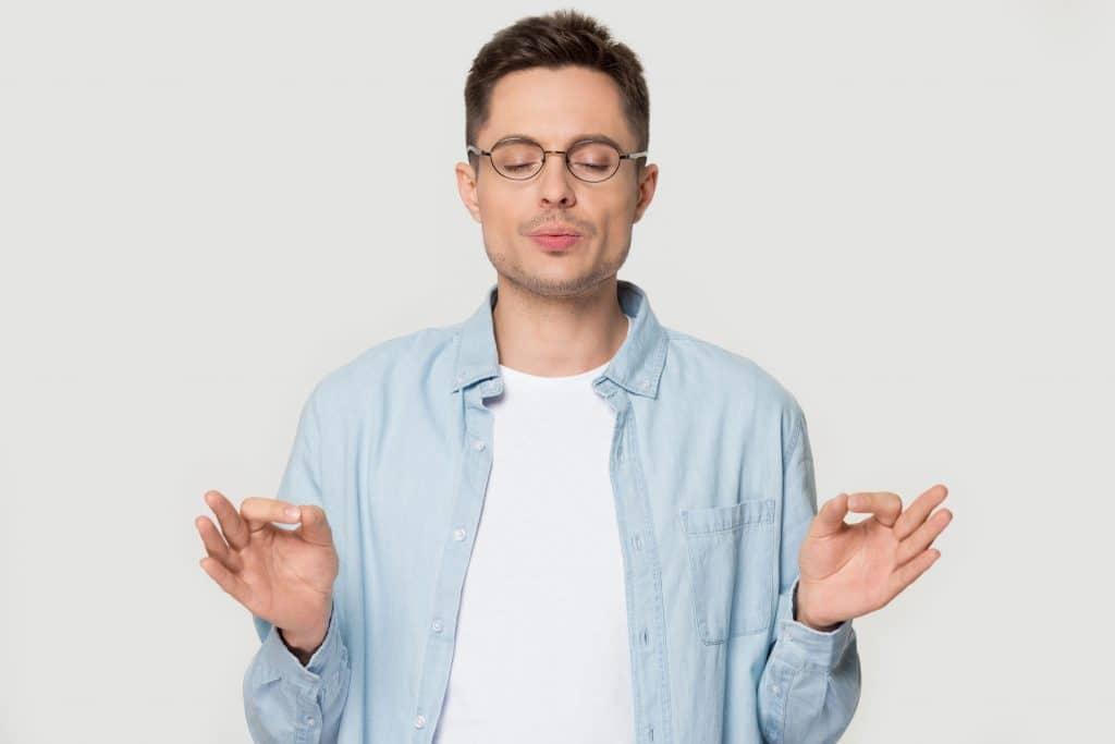 Homem branco, jovem, com óculos, de olhos fechados, respirando fundo, com as mãos em posição de meditação, tentando se acalmar.