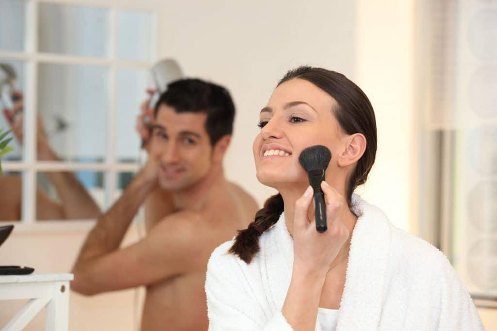 Mulher se maquiando no banheiro de casa, passando blush olhando para o espelho, enquanto seu parceiro seca o cabelo com secador e observa-a com olhar apaixonado
