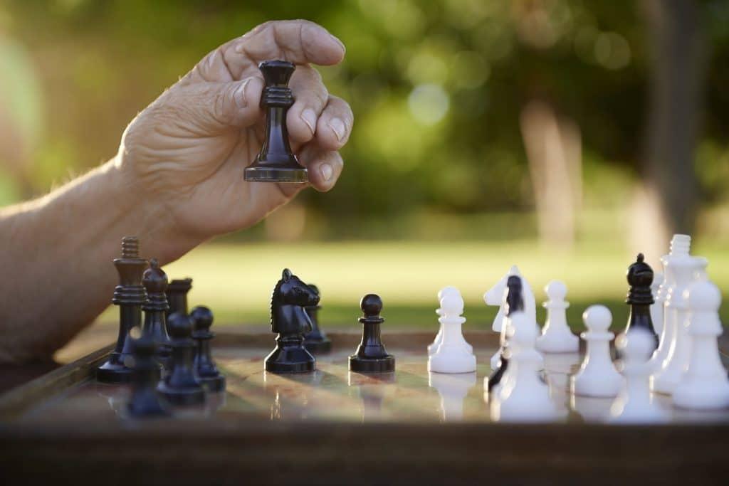 Mão de homem jogando xadrez em um parque