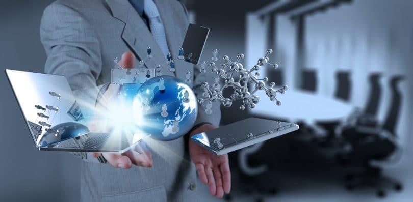 Elementos tecnológicos flutuam ao redor da mão de um homem com terno em uma sala de escritório.