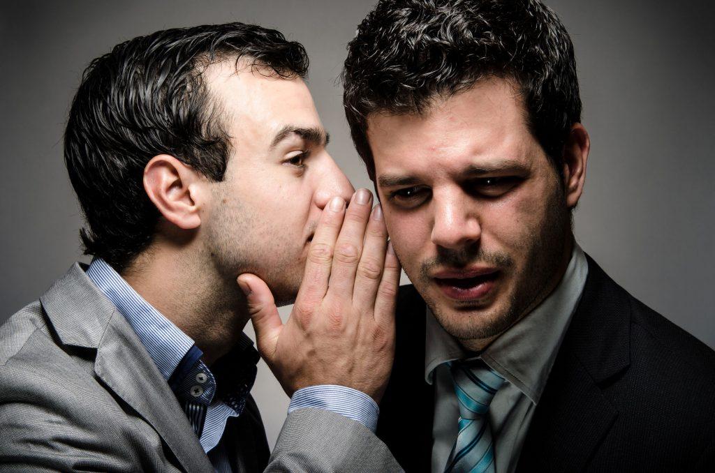 Dois homens brancos, vestindo roupas sociais, conversando, um cochichando no ouvido do outro, contando uma fofoca.