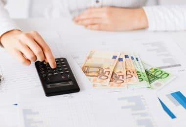 Mesa com vários papéis, notas de dinheiro e uma calculadora. Uma pessoa faz cálculos.
