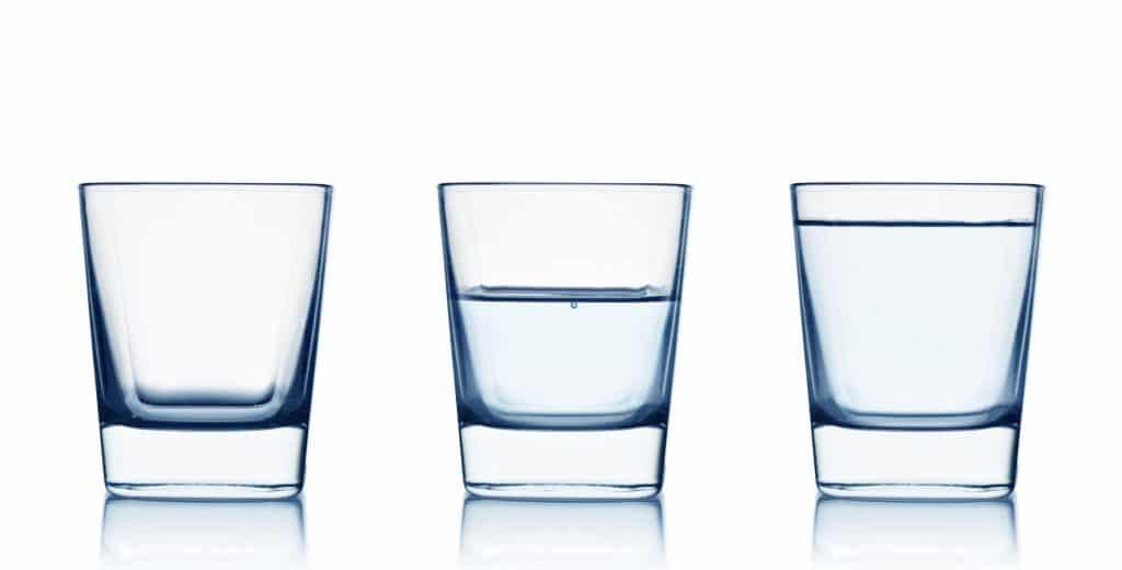 Três copos. Um está vazio. Outro está com água pela metade. O último está cheio de água. Simboliza o otimismo.