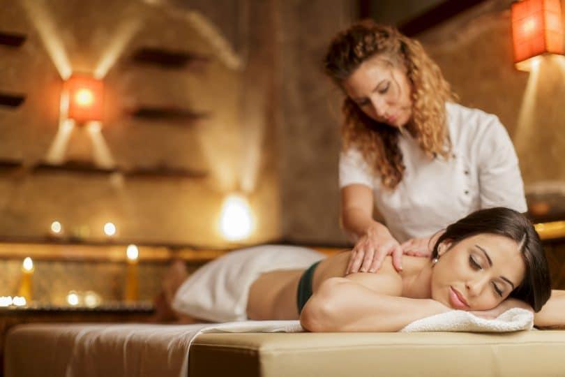 Terapeuta fazendo massagem em paciente deitada relaxada na maca