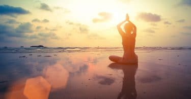 Mulher na beira da praia sentada em posição de ioga com céu ao fundo e luz do refletida