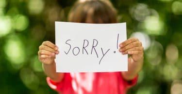 """Mãos de criança segurando plaquinha escrito """"Sorry!"""" no foco e criança desfocada ao fundo"""