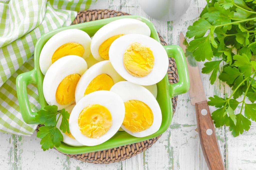 tigela verde com ovos cozidos cortados ao meio, em cima de uma mesa de madeira
