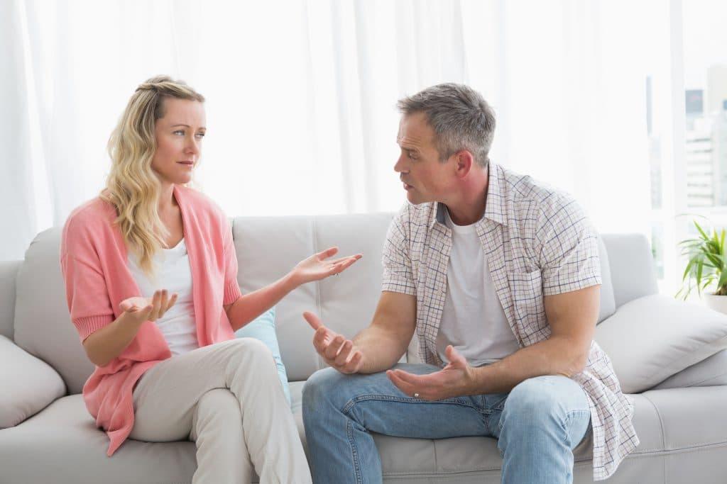 Casal, de homem e mulher, conversando sentados em um sofá cinza