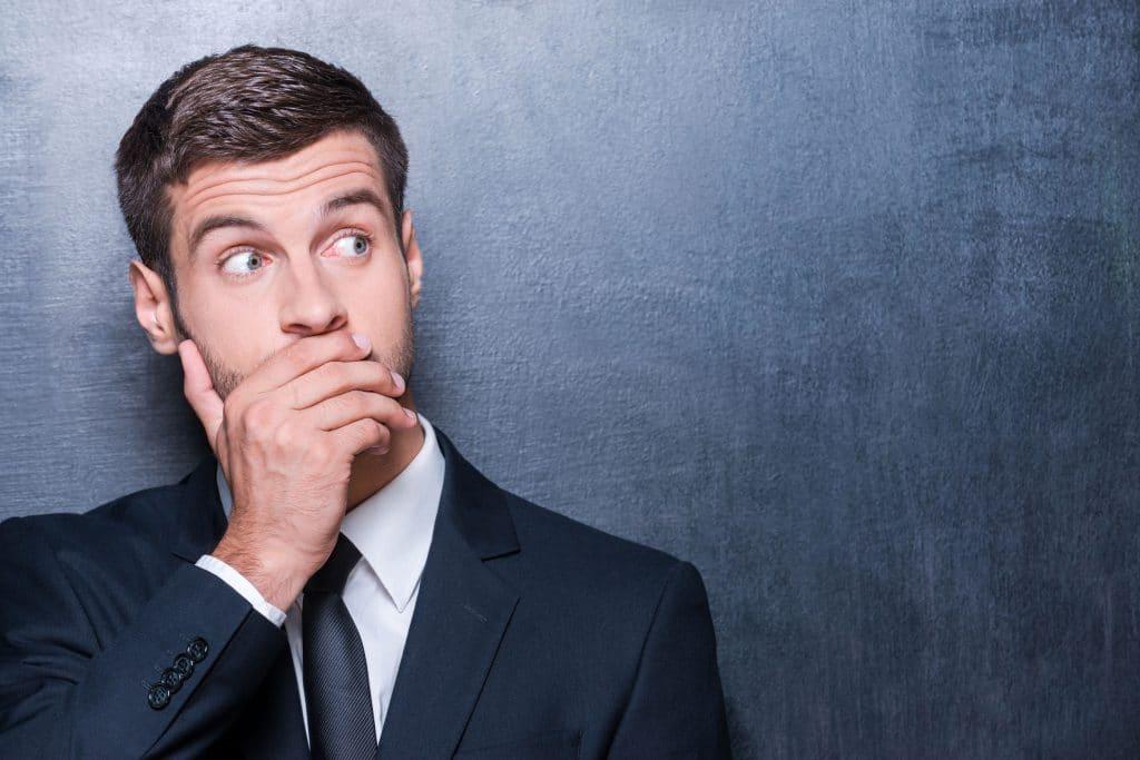 Homem branco, usando roupas sociais, cobrindo sua boca com a mão