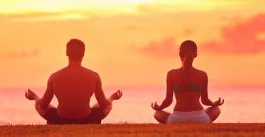 Retiro de imersão : Duas pessoas, homem e mulher, sentados na grama, com as pernas cruzadas, meditando ao pôr do sol.