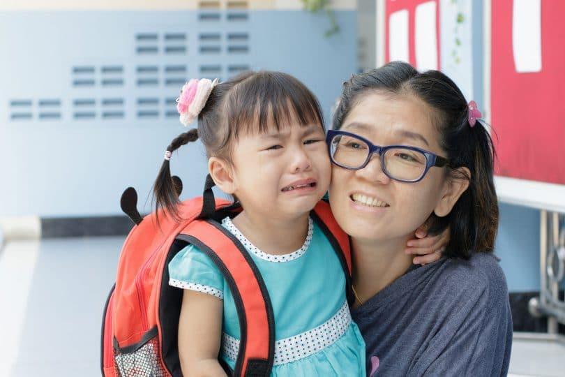 Mãe e filha no primeiro dia de escola, filha pequena chorando