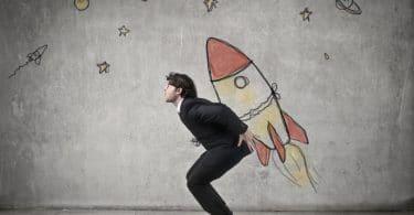 Homem agachado com um foguete em desenho nas costas