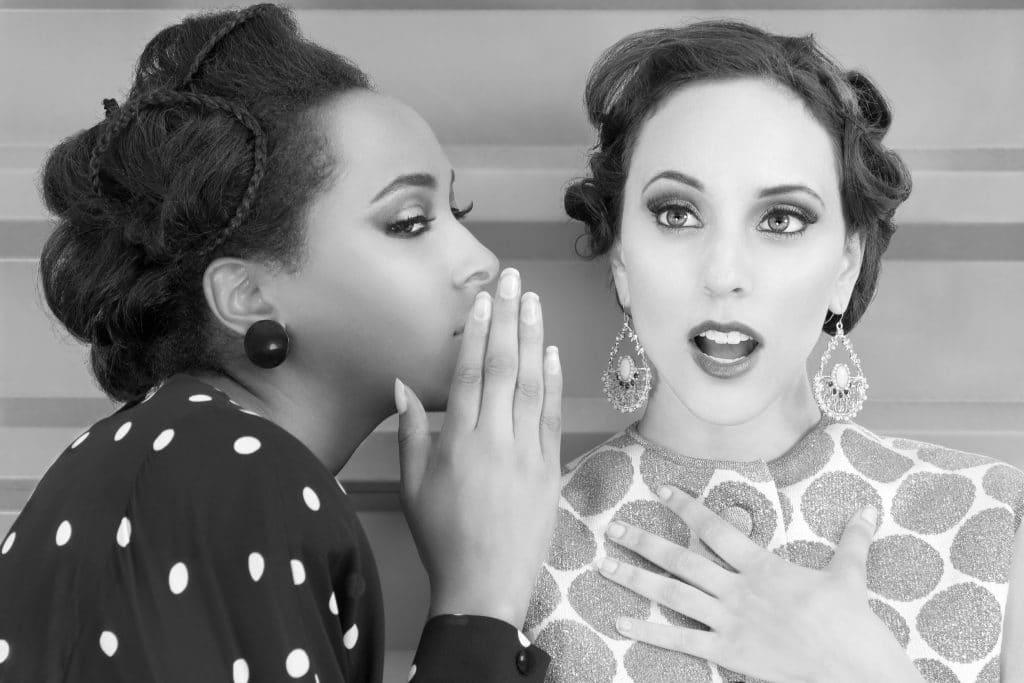 Foto em preto e branco de duas mulheres, uma negra e uma branca, ambas com roupas e penteados antigos. Elas estão conversando, a mulher negra está cochichando algo no ouvido da mulher branca.