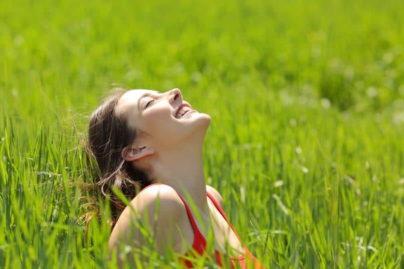 Garota feliz sentada no meio da grama alta com rosto para cima e olhos fechados iluminada pelo sol