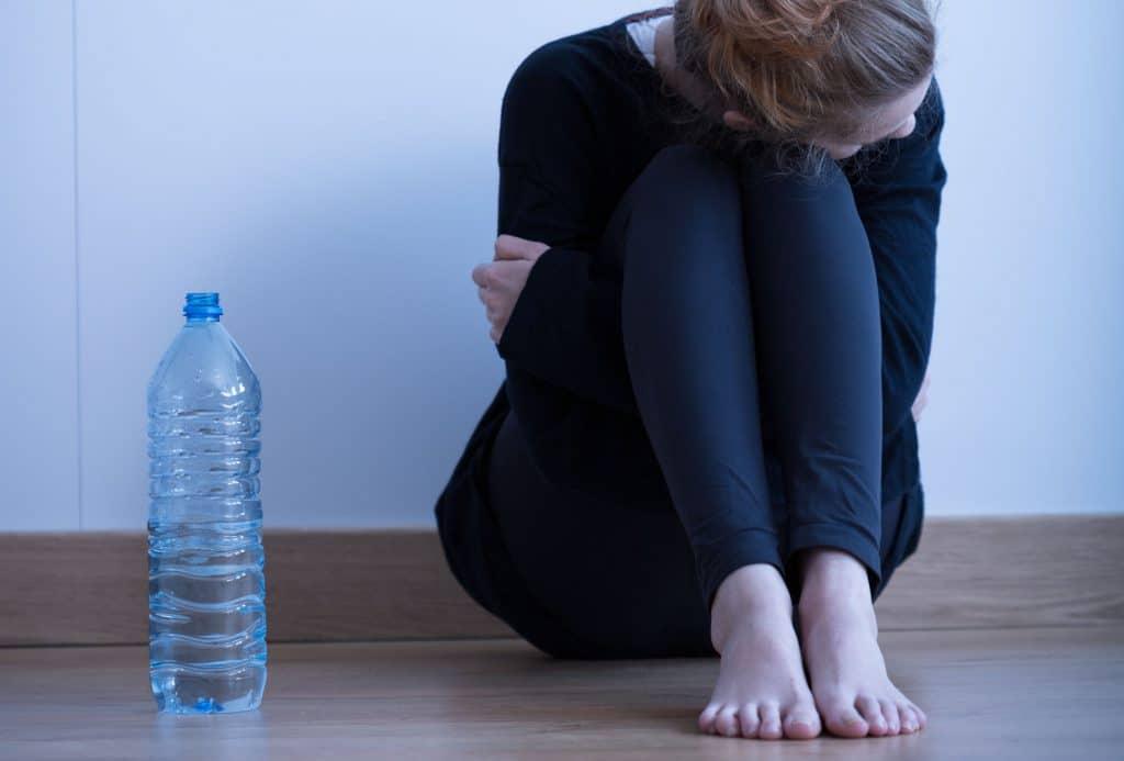 mulher branca, vestindo roupas pretas, sentada no chão de madeira de uma casa, encolhida, abraçando seus joelhos