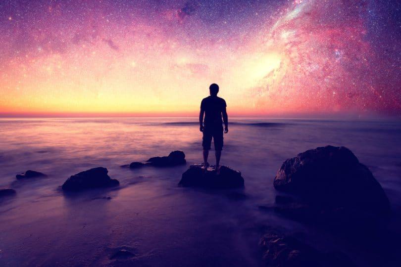 Silhueta de um homem olhando para o céu estrelado.