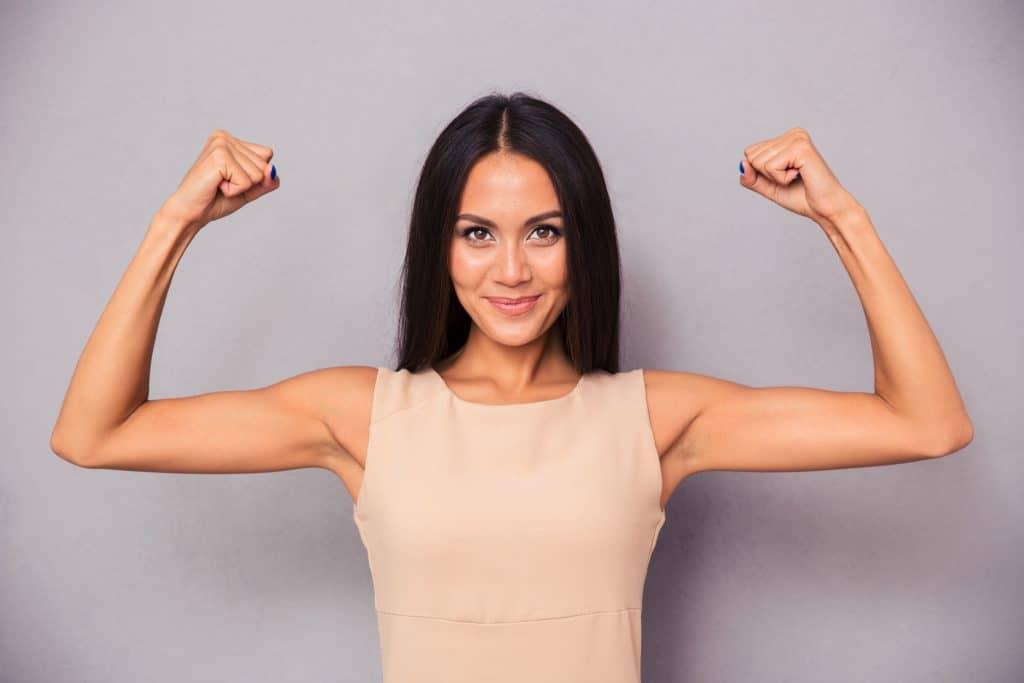 Mulher feliz mostrando seus bíceps simbolizando força e coragem.
