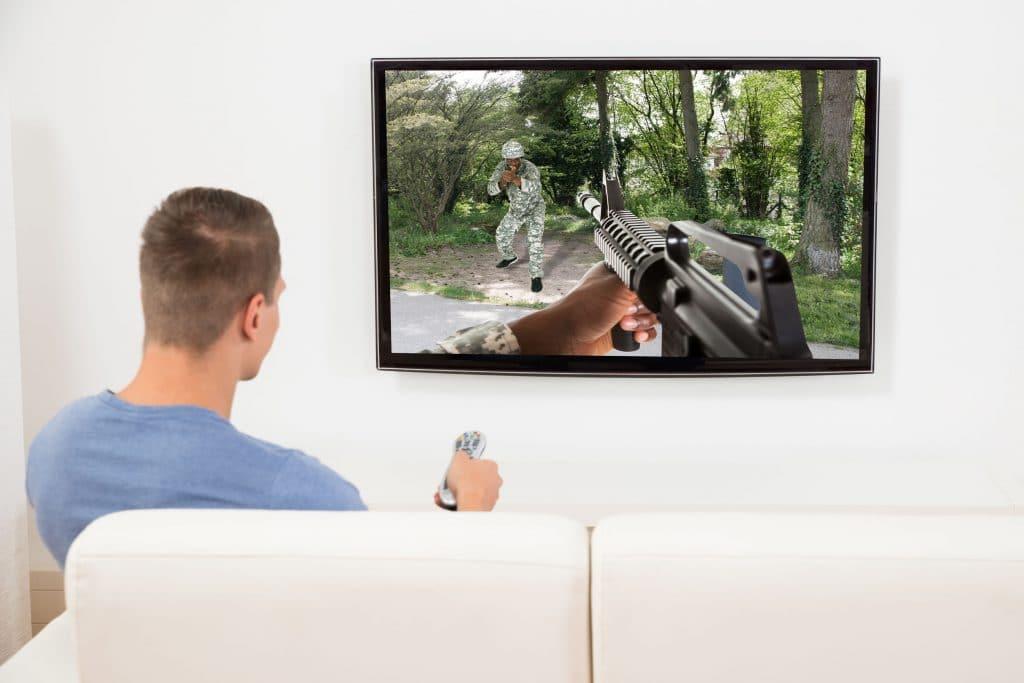 Rapaz jovem sentado em um sofá, assistindo um filme violento, com pessoa atirando