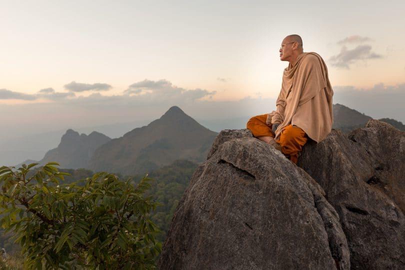 Monje budista meditando sobre montanhas.