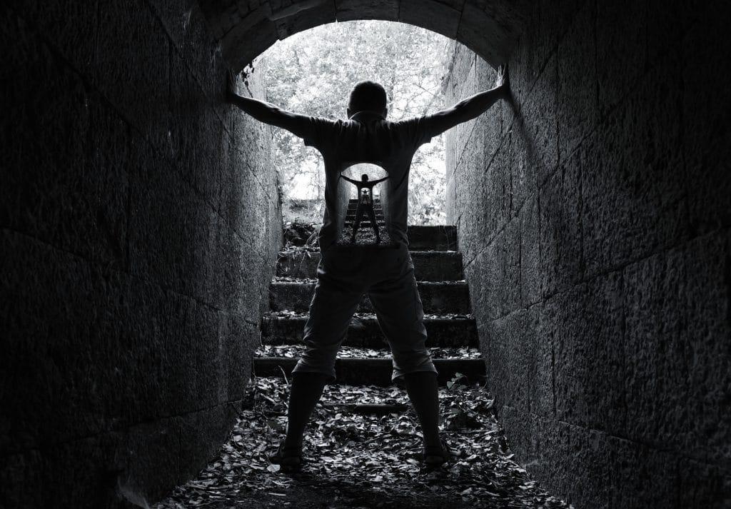 Ilustração preta e branca de pessoa segurando as paredes de um túnel