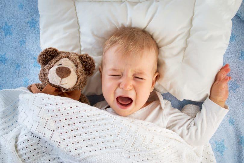 Bebê dormindo com um ursinho ao lado e chorando durante o sono.