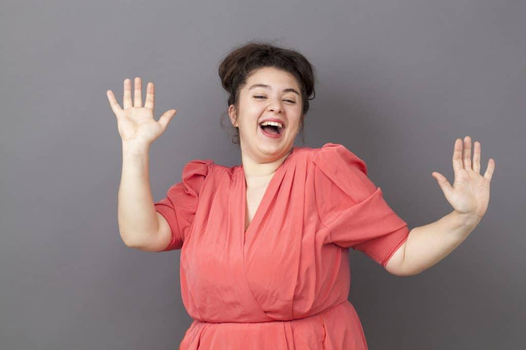 Mulher branca, gorda, vestindo um vestido salmão, sorridente, em frente à uma parede cinza