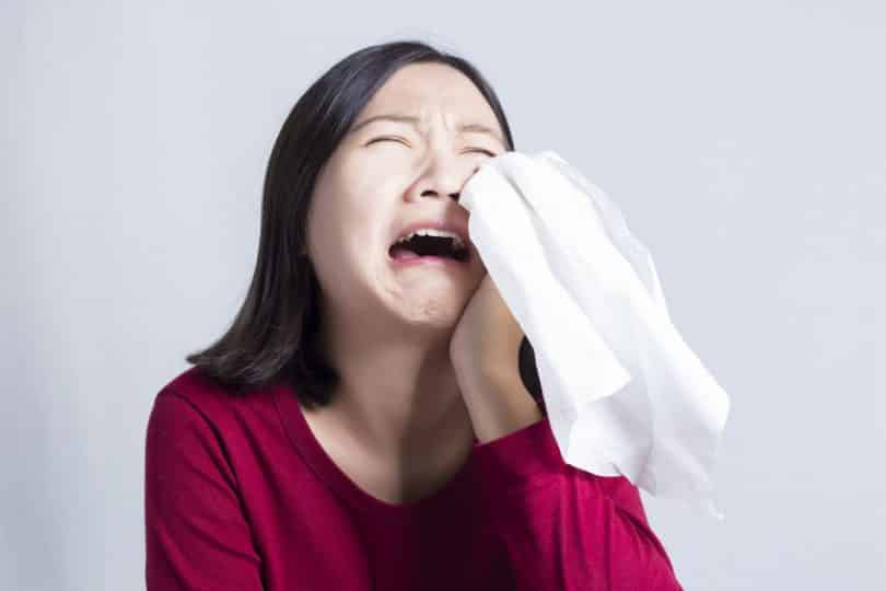 Mulher chorando com lenço secando as lágrimas