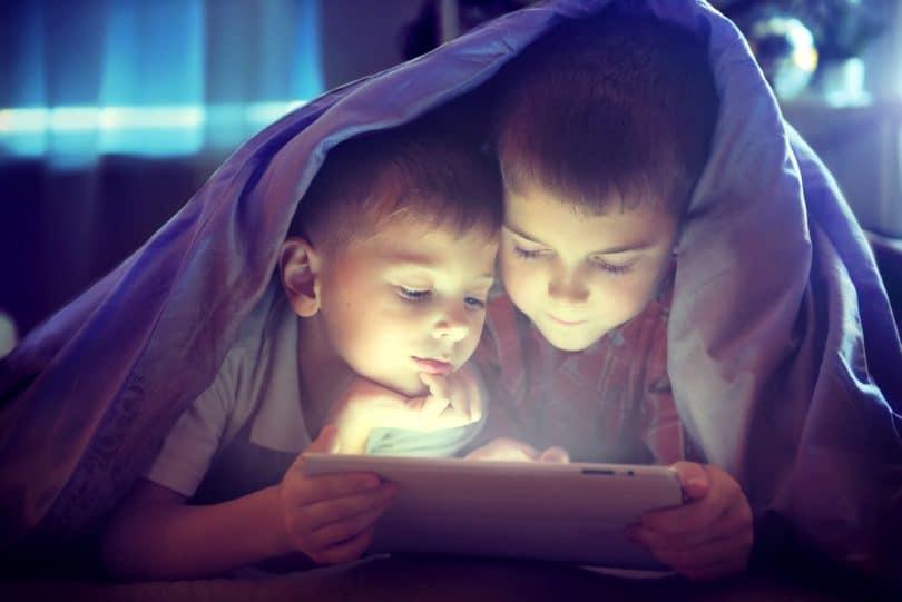 Duas crianças mexendo em um tablet embaixo das cobertas.