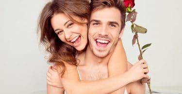 Casal jovem alegre com abraçando o pescoço por trás com rosa na mão